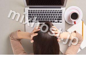 パソコンで頭を抱える女性